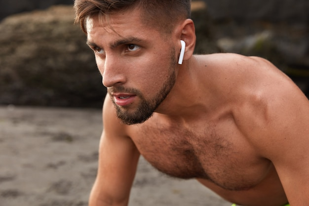 Close up de um homem com a barba por fazer auto-determinado olhando de lado