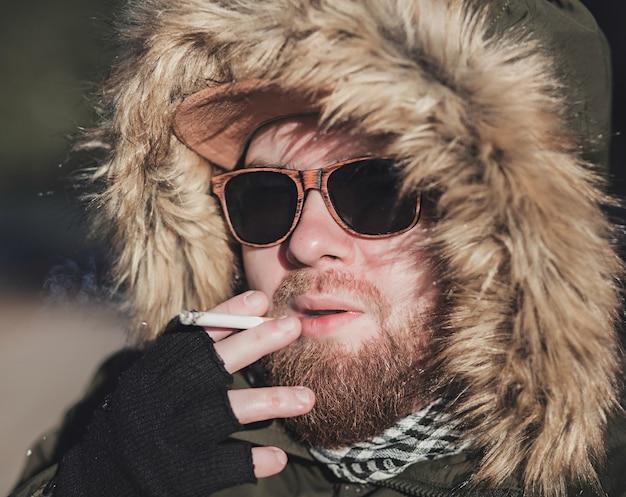 Close-up de um homem com um cigarro ao ar livre. mau hábito