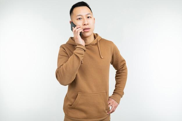Close-up de um homem de aparência asiática no capuz marrom casual, falando ao telefone sobre um fundo branco, com espaço de cópia