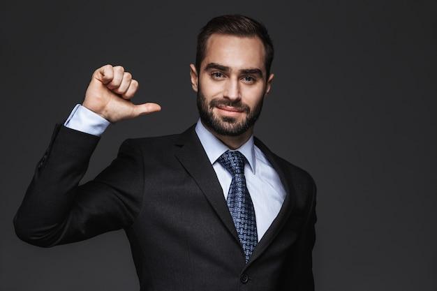 Close-up de um homem de negócios jovem e bonito vestindo terno, isolado, apontando para si mesmo