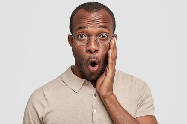 Close up de um homem de pele escura espantado com a boca bem aberta