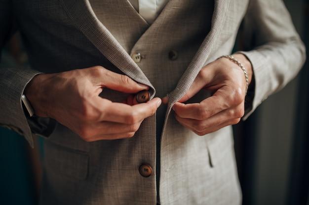 Close-up de um homem de smoking consertando o botão de punho