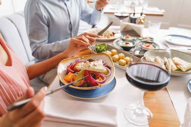 Close-up de um homem e uma mulher sentados à mesa e comendo comida deliciosa no café