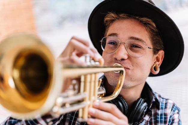 Close-up de um homem elegante de jazz tocando trompete muito apaixonado