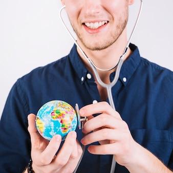 Close-up, de, um, homem, examinando, globo, com, estetoscópio