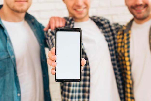 Close-up, de, um, homem, ficar, com, seu, dois amigos, mostrando, telefone móvel, com, branca, tela, exposição