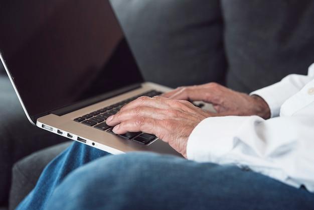 Close-up, de, um, homem idoso, mão, digitando, ligado, laptop