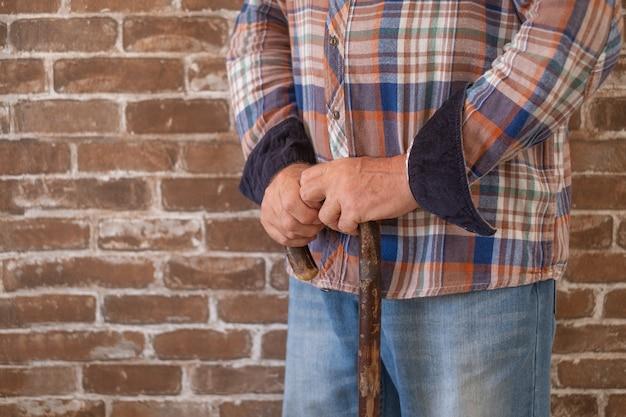 Close-up de um homem idoso sofrendo, andando com a ajuda de uma bengala.