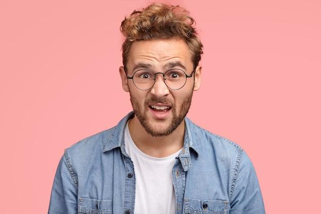 Close up de um homem indignado e estupefato com cabelo encaracolado olhando desesperadamente para a câmera, usando óculos redondos para uma boa visão