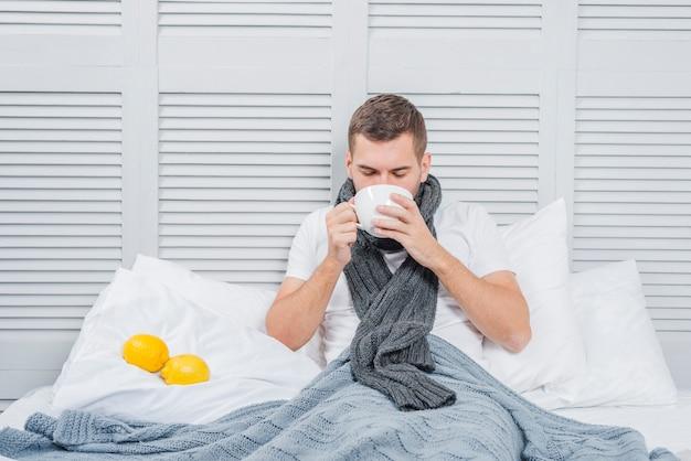 Close-up, de, um, homem jovem, sentar-se cama, bebendo, a, xícara café