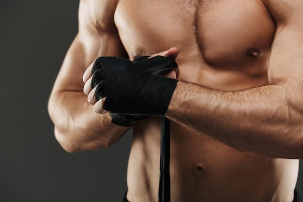 Close-up de um homem musculoso, amarrando ataduras de boxe