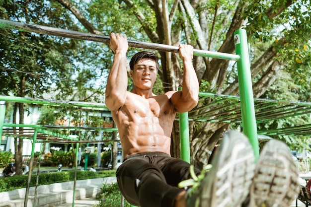 Close-up de um homem musculoso asiático sem roupas fazendo exercícios de flexão em l usando uma barra de ferro no parque