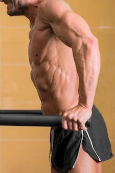 Close-up de um homem musculoso fazendo mergulho de tríceps em barras paralelas na academia