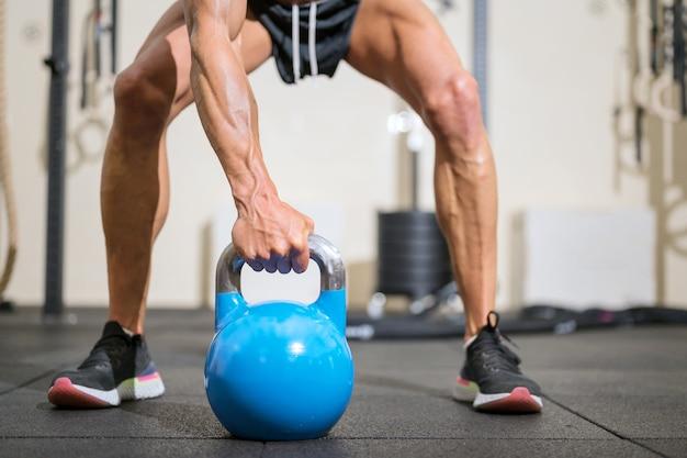 Close-up de um homem musculoso levantando um kettlebell pesado