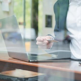 Close-up, de, um, homem negócios, com, laptop, ligado, tabela, usando, cartão crédito, em, café