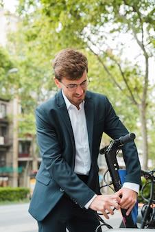Close-up, de, um, homem negócios, trancar, a, scooter elétrico, em, rua