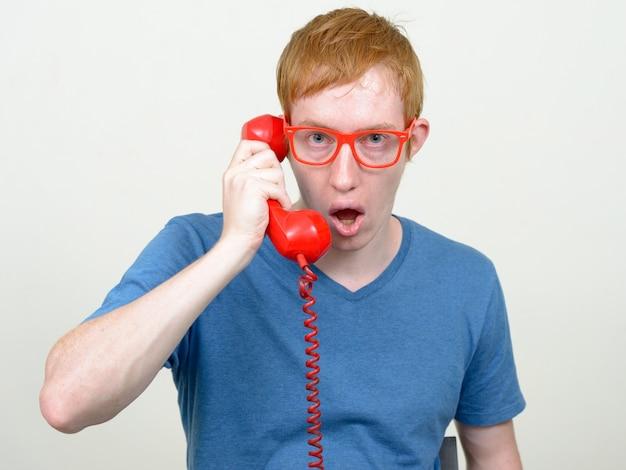 Close-up de um homem nerd com cabelo vermelho e óculos isolados