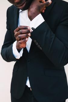 Close-up, de, um, homem preto, em, um, smoking, afixando, seu, cufflinks.groom, gravata borboleta, abotoaduras