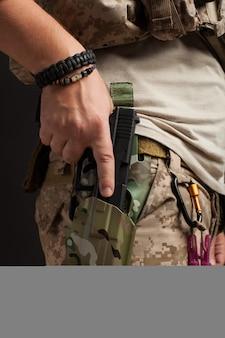 Close-up de um homem puxa uma arma de seu coldre.