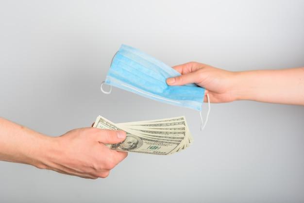 Close-up de um homem que compra uma máscara médica. o conceito de alta demanda. vendendo máscaras médicas azuis por dólares.