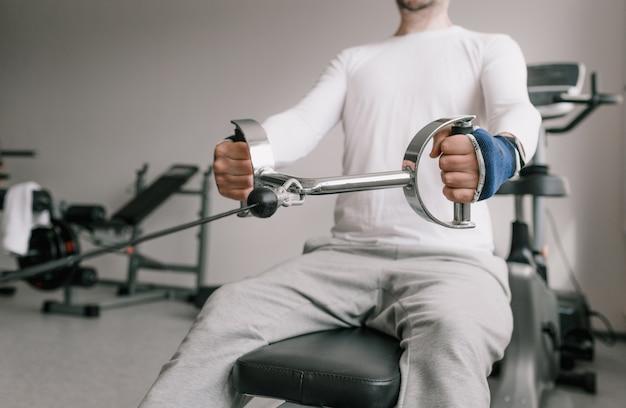 Close-up de um homem realizando tração em uma máquina de musculação. treino intenso no ginásio