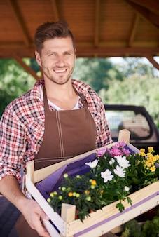 Close-up de um homem segurando um baú cheio de flores coloridas