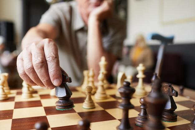 Close-up de um homem sênior caucasiano jogando xadrez e desfrutando de atividades no espaço de cópia do lar de idosos