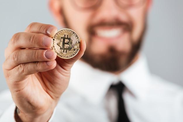Close-up de um homem sorridente, mostrando o bitcoin dourado