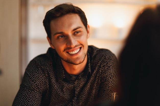Close-up de um homem sorridente, sentado à mesa, olhando para a mulher dentro de casa