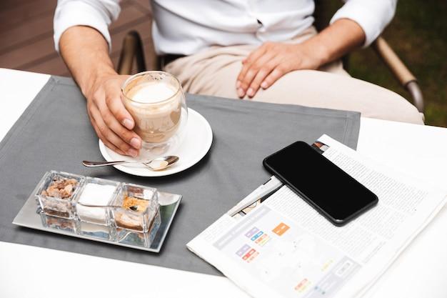 Close-up de um homem tomando café enquanto está sentado