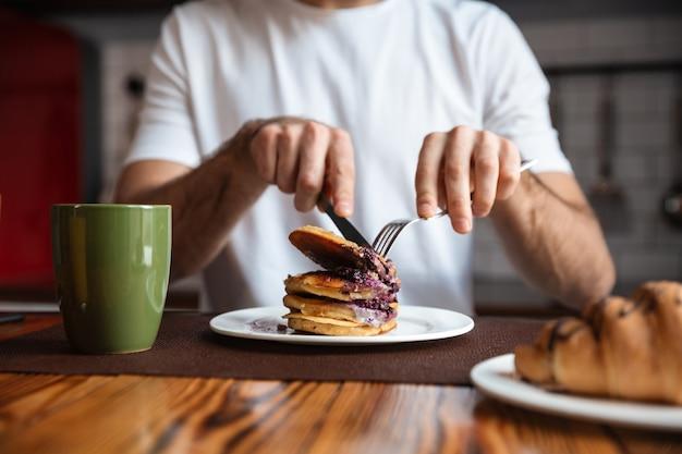 Close-up de um homem tomando panquecas no café da manhã na mesa da cozinha