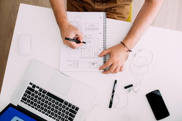 Close-up de um homem trabalhando na mesa do escritório, desenhando no bloco de notas