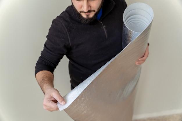 Close-up de um homem usando um rolo de pano isolante para instalar um piso de madeira