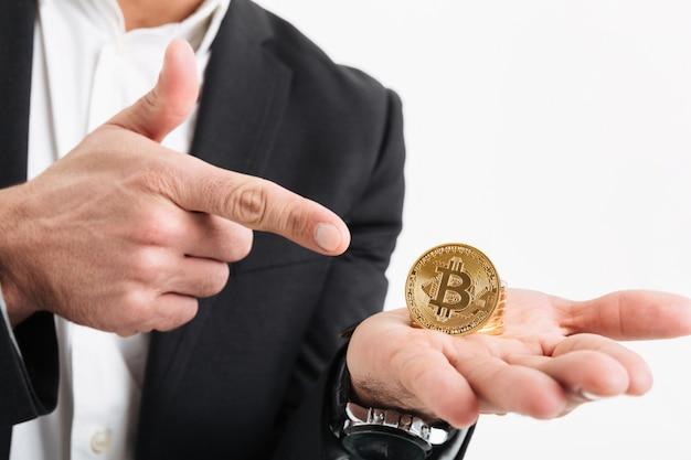 Close-up de um homem vestido de terno segurando bitcoin