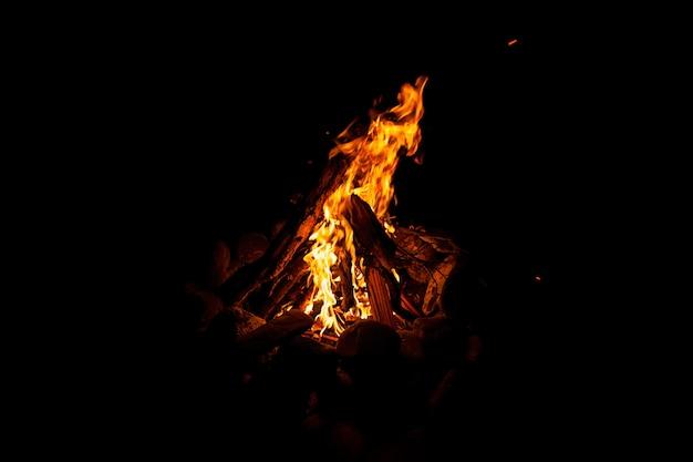 Close-up de um incêndio com uma chama laranja e vermelha queimando no escuro