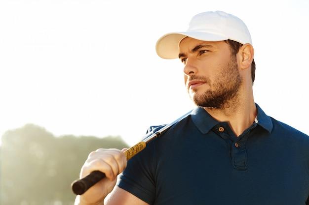 Close-up de um jogador de golfe masculino bonito segurando o taco de golfe