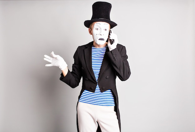 Close-up de um jovem ator falando no celular para o fundo cinza.