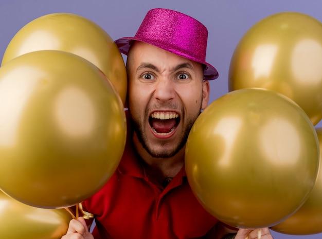 Close-up de um jovem bonito e furioso com um chapéu de festa, olhando para a frente, segurando balões isolados na parede roxa