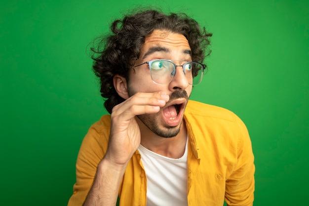 Close-up de um jovem bonito impressionado de óculos olhando para o lado tocando o rosto isolado na parede verde