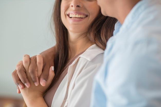 Close-up de um jovem casal inter-racial abraçando com amor em casa - menino e menina milenar da vida juntos em um relacionamento abraço e toque com afeto - conceito de novo homem e mulher de casa