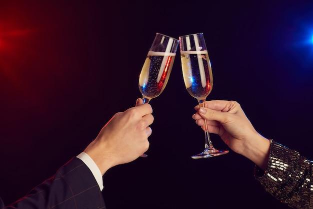 Close-up de um jovem casal tilintando taças de champanhe iluminadas por luzes de festa contra um fundo preto filmado com flash