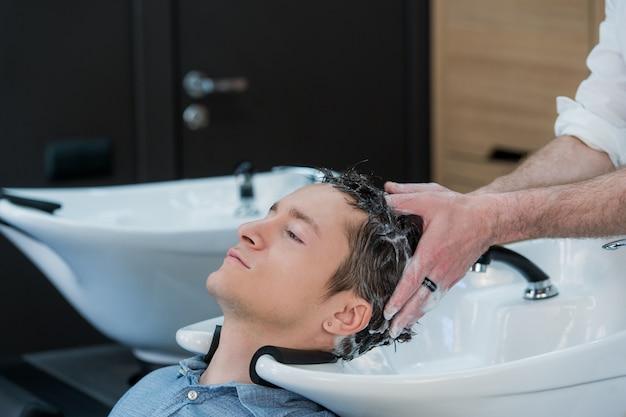 Close-up de um jovem com o cabelo lavado no salão de cabeleireiro