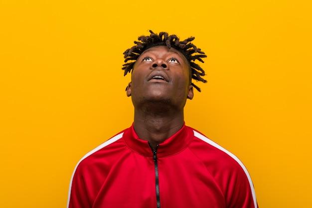 Close-up de um jovem desportivo africano em pé contra uma parede amarela