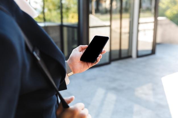 Close-up de um jovem empresário vestindo terno olhando para a tela em branco do celular ao ar livre