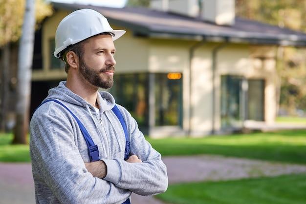 Close-up de um jovem engenheiro com capacete, olhando para longe, posando com os braços cruzados