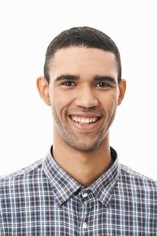 Close-up de um jovem feliz vestindo uma camisa xadrez em pé sobre o branco