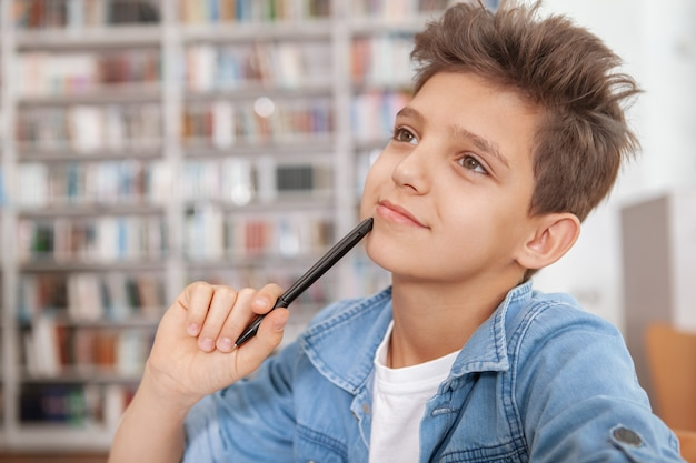 Close-up de um jovem garoto encantador que gosta de estudar na biblioteca, olhando para longe, pensativo