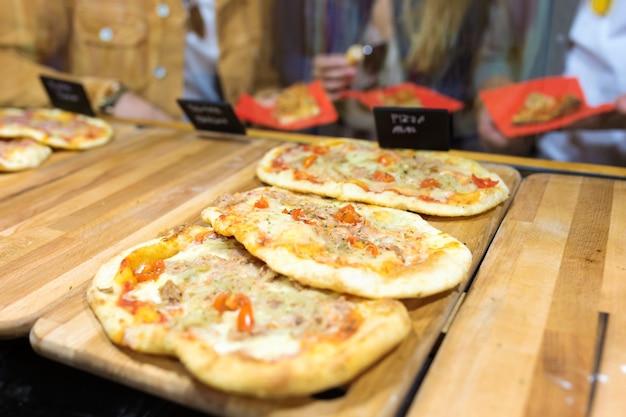 Close-up de um jovem grupo de amigos, visitando e comprando pizza em comer mercado na rua.