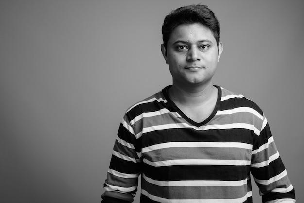 Close-up de um jovem indiano vestindo uma camisa listrada de manga comprida