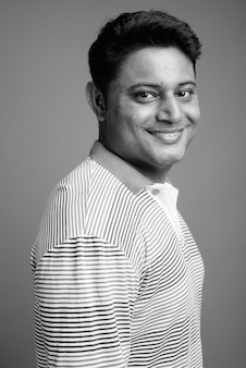 Close-up de um jovem indiano vestindo uma camisa pólo listrada de manga comprida